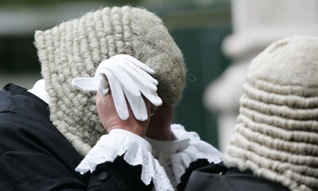 A judge adjusts his wig