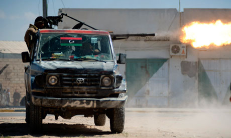 Libyan rebels fire a heavy machine gun mounted on a pick-up truck during heavy clashes