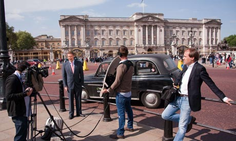 A television crew record a piece to camera outside Buckingham Palace, London