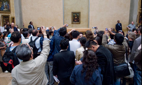 Tourists photographing the Mona Lisa by Da Vinci
