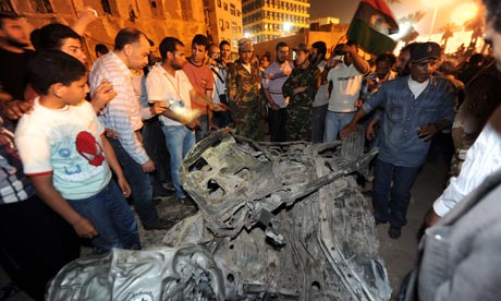 Libyan rebels gather around the remains of car which exploded in Benghazi