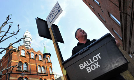 man with ballot box underneath polling station sign