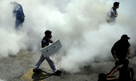 Demonstrators wearing gas masks walk amid tear gas during clashes with police, Greece