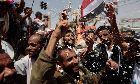 Anti-government protesters spray foam and wave the national flag as they celebrate in Yemen