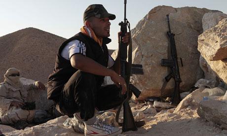 Rebel Libyan fighters face Gaddafi loyalist troops near Bir Ghanem