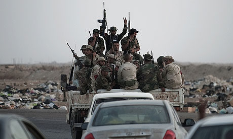Libyan rebel fighters drive towards the Brega frontline