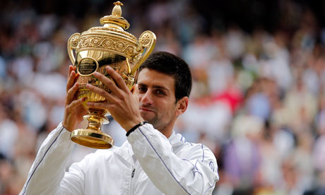 Novak Djokovic hoists the championship trophy following his victory at Wimbledon Championships