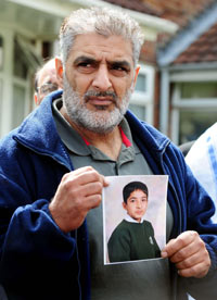 Tariq Jahan holds a picture of his son Haroon Jahan, Birmingham