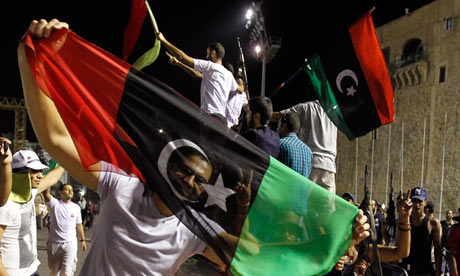 A Libyan holds the Kingdom of Libya flag as he celebrates w fellow Libyans at Green Square Tripoli