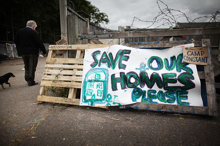 Dale Farm: 30 August 2011: A traveller walks past a 'save our homes' sign