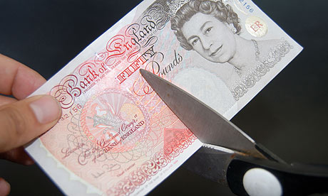 Fifty pound note being cut with scissors
