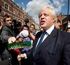 Boris Johnson addresses the crowd holding a broom in Clapham