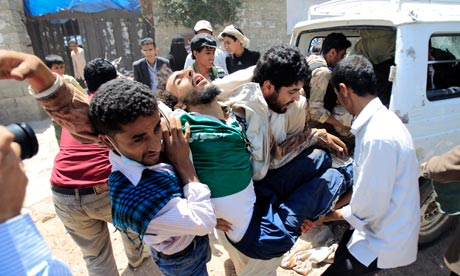 Medics carry a wounded anti-government protester in Sanaa