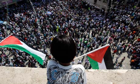 A Palestinian boy holds a flag as he watches a rally in Ramallah