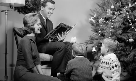 1960s Family Father Mother Two Sons Sitting By Christmas Tree In Living Room Reading A Book