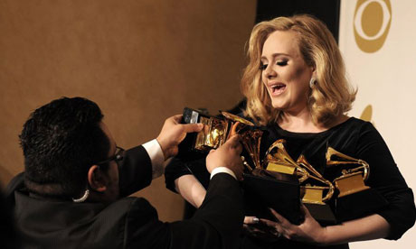 British singer Adele is helped with her clutch of Grammy awards
