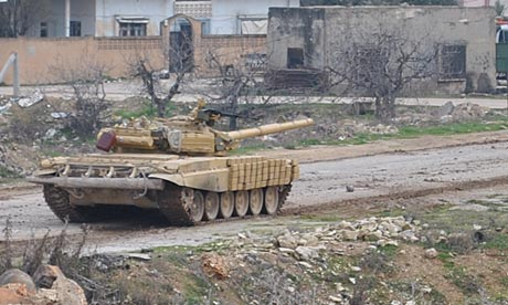 A Syrian forces tank moving along a road during clashes with the Syrian army defectors