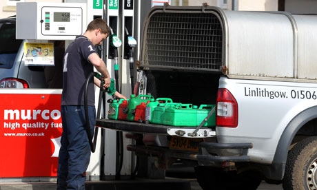 A man fills up jerry cans in a panic at a petrol station in Linlithgow