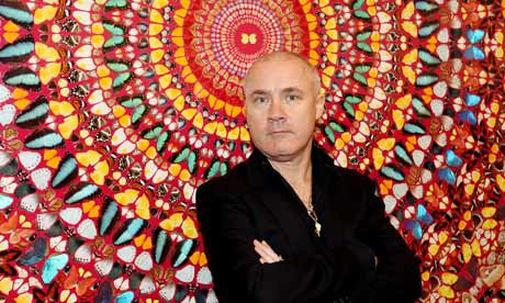 Artist Damien Hirst poses in front of his artwork in the Tate Modern