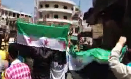 A Syrian man holds the revolutionary flag during a demonstration in Hama
