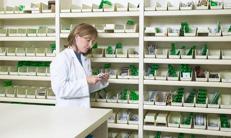 View of a female pharmacist examining a pill packet