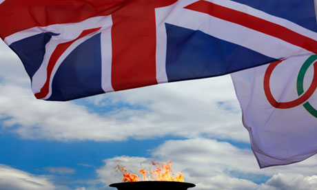 A British flag and an Olympic flag fly next to the Olympic flame in a cauldron atop the Acropolis