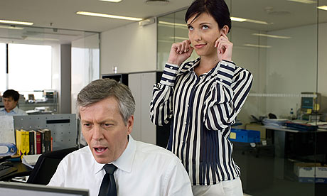 Man in office looking into computer and complaining, woman standing behind with finger in ears