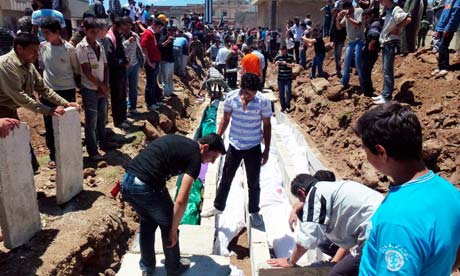 People gather at a mass burial for the victims in Syria