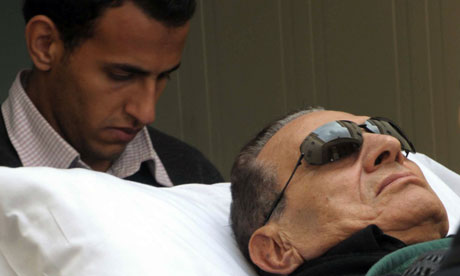 Former Egyptian president Hosni Mubarak being wheeled on a stretcher into court for his trial