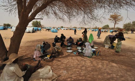Refugees from northern Mali sit under a