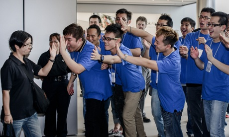 The staff look more excited than the customer as they greet the first person to arrive in the Apple store in Hong Kong to buy an iPhone 5.  The launch of Apple's iPhone 5 has seen long queues of shoppers around the world undeterred by a lukewarm welcome from experts for the smartphone and complaints about its new mapping system.