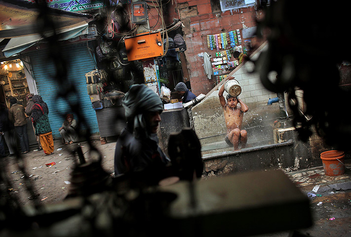 Cold weather in India: A man washes at an outdoor basin on a cold morning