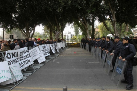 Police officers stand guard in front of protesters during an anti-bailout rally by employees of Cyprus Popular Bank outside the parliament in Nicosia March 22, 2013.