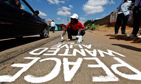 Kenyan street artist Solo7 paints message of peace near a polling station in Kibera slum of Nairobi