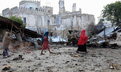 Somali women walk past the site of a deadly blast in Mogadishu