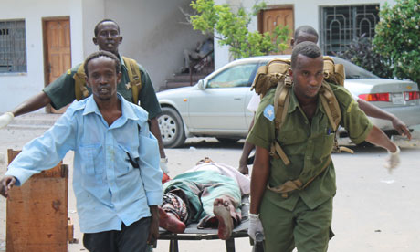 Soldiers carry a wounded civilian from the entrance of the court in Mogadishu
