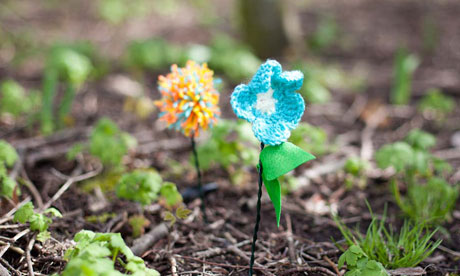 knitted flowers planted in the ground