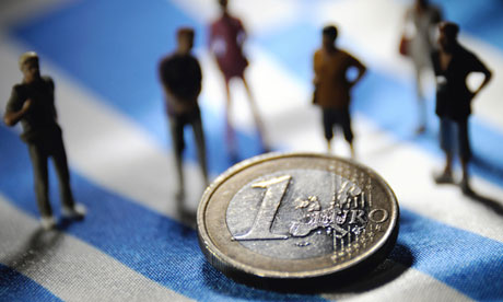 Figurines and a euro on a Greek flag