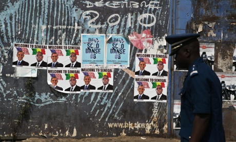 A policeman walks past posters of US President Barack Obama and Senegalese President Macky Sall in anticipation of Obama's arrival in Dakar.