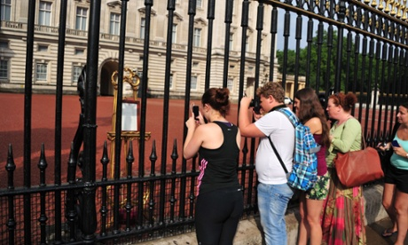 Tourists take pictures of the easel announcing the royal birth.