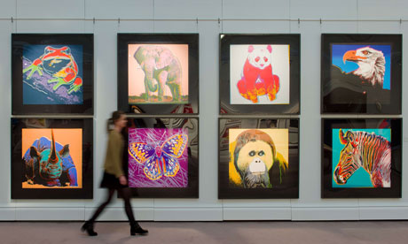 A gallery assistant walks in front of US US artist Andy Warhol's 1983 Endangered Species