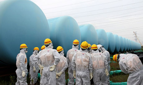 Staff of Japan's nuclear regulator near storage tanks for radioactive water at Fukushima Daiichi