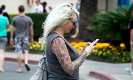 A woman texting on her mobile phone while walking