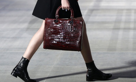 model carries snakeskin-effect bag on the catwalk in Tokyo