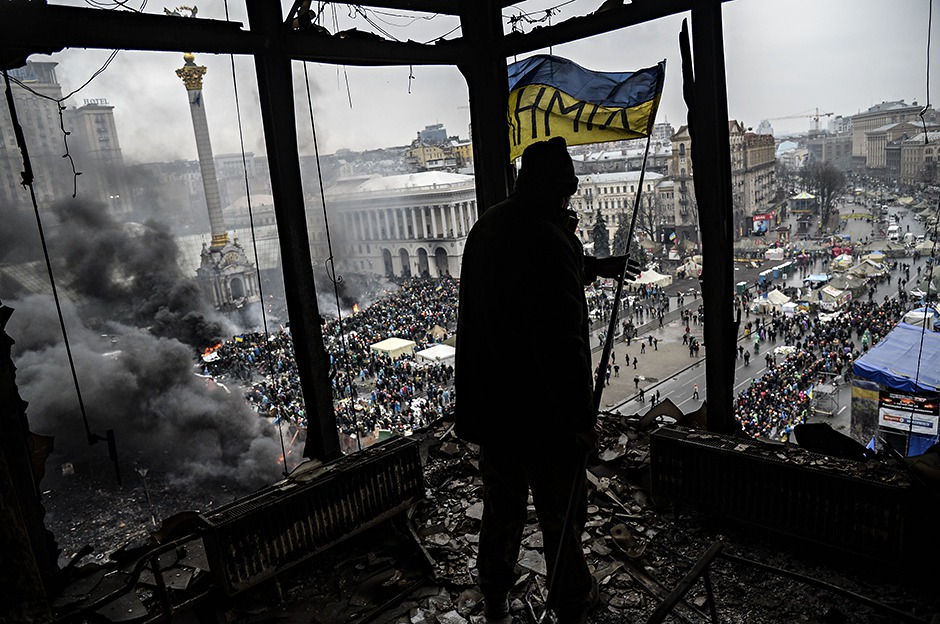 A demonstrator stands on a balcony of a burnt-out building in Kiev