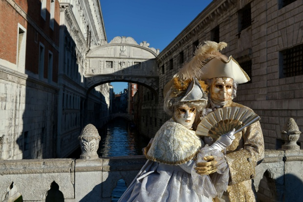 Costumed revellers pose in front the Bridge of Sighs during the carnival in Venice. The 2014 edition of the Venice carnival is untitled