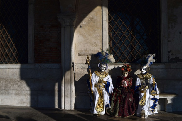 Costumed revellers pose in St Mark's square during the carnival in Venice.  Photograph: Gabriel Bouys/AFP/Getty Images