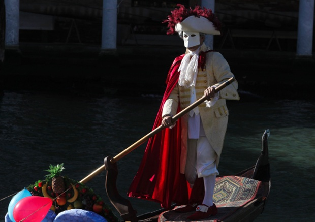 A man wearing a mask navigates a boat through a canal during the carnival in Venice. Photograph: Stringer/Reuters