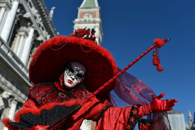 A costumed reveller poses in St Mark's square during the carnival in Venice. Photograph: Gabriel Bouys/AFP/Getty Images