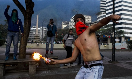 A demonstrator throws an incendiary device during clashes with Venezuelan National Bolivarian Guard (GNB) during a prote